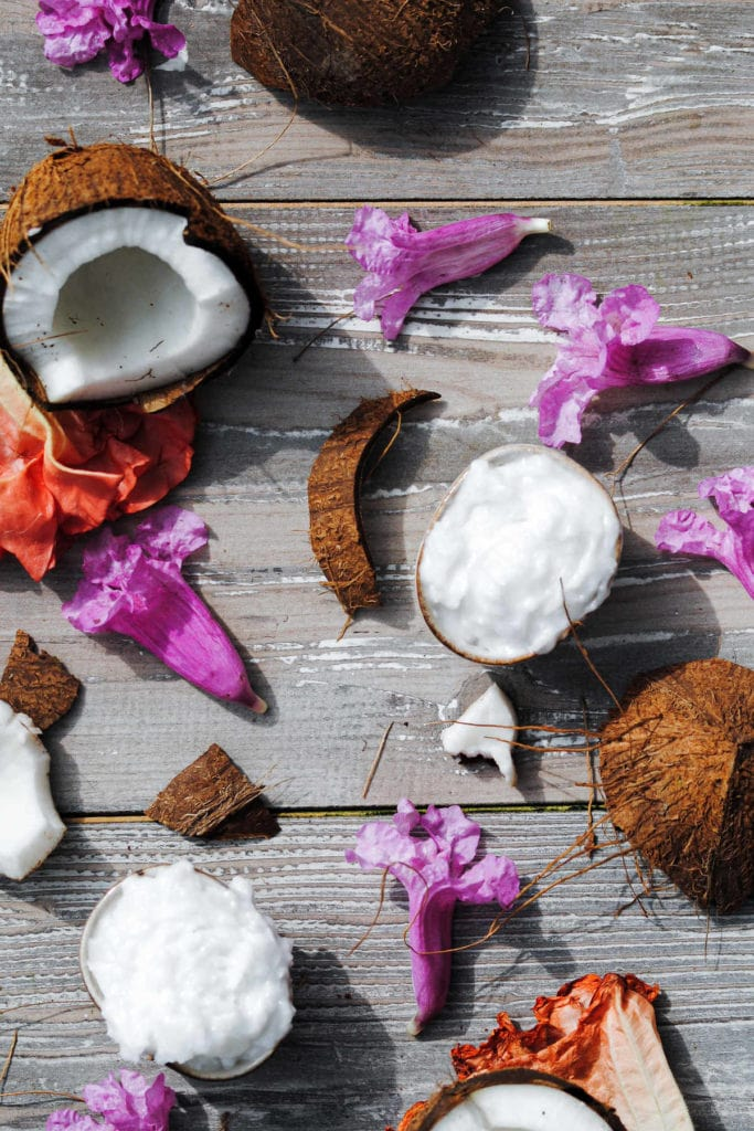 two little pinch bowls filled with coconut oil surrounded by coconuts and flowers