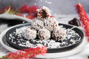 stack of coconut covered energy balls with bite taken out of top and coconut flakes falling down