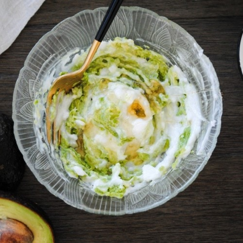 mixing together mashed avocado, honey, and coconut oil hair mask in a bowl