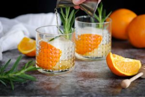 pouring bourbon into old fashioned glass with whiskey ice