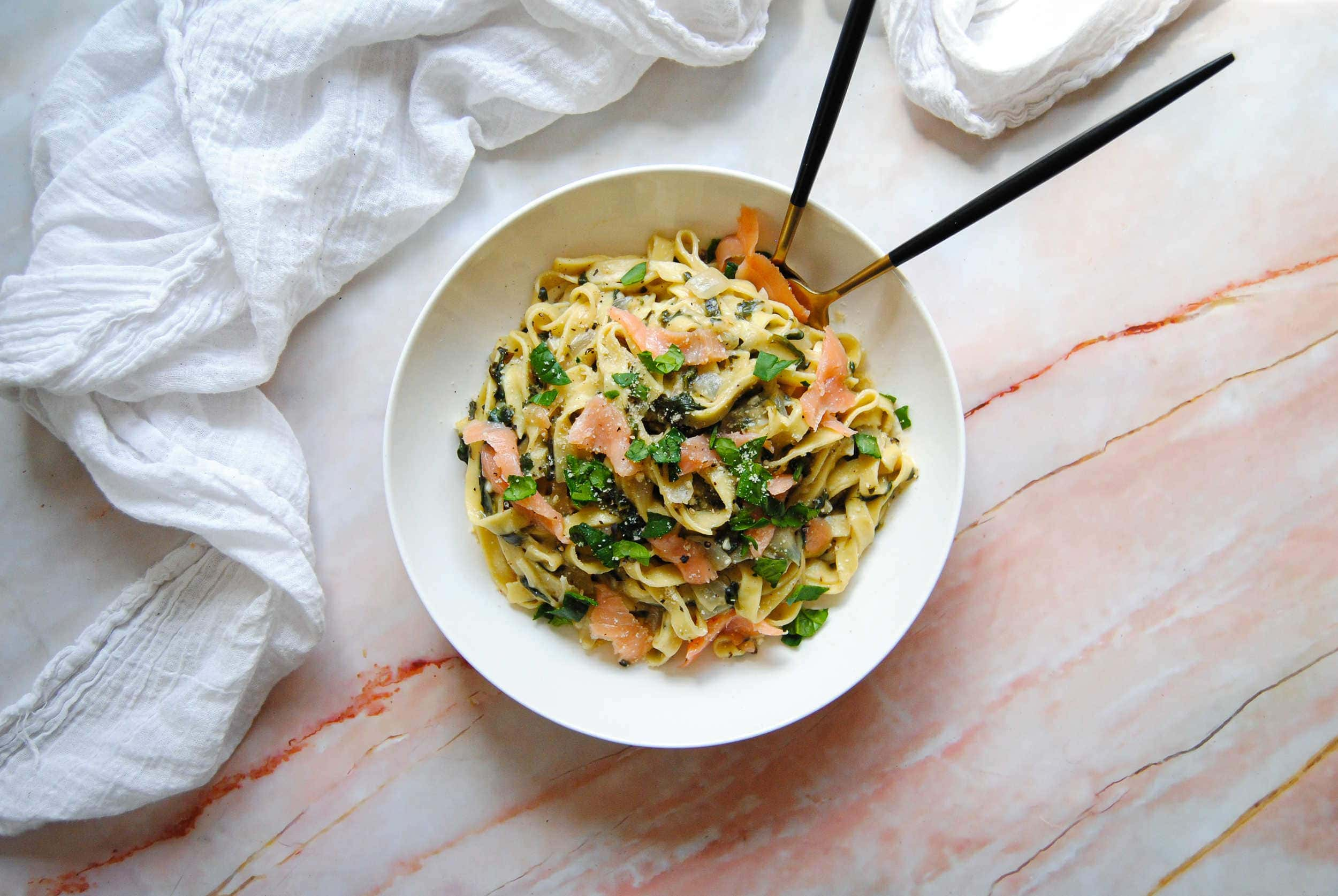 overhead shot of smoked salmon with parmesan pasta with fork and spoon