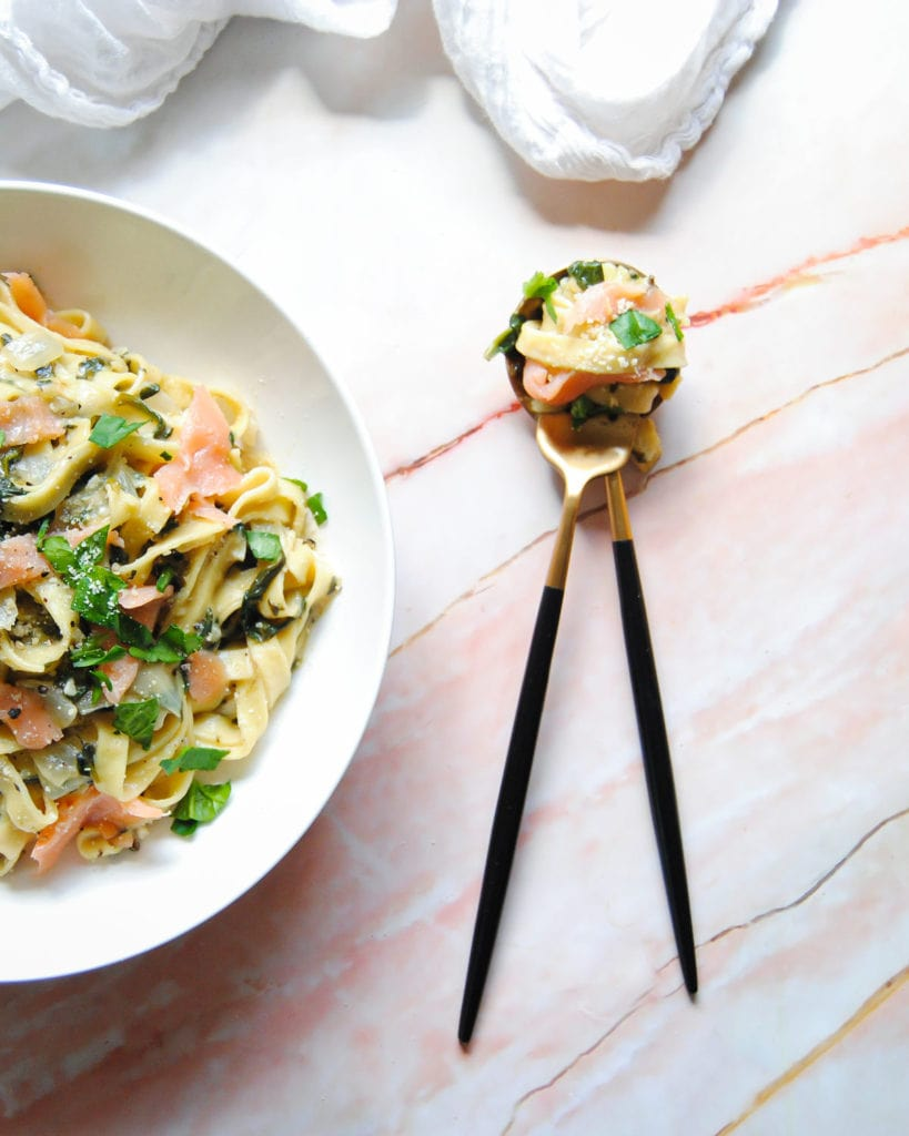 fork and spoon with pasta and smoked salmon twirled around it