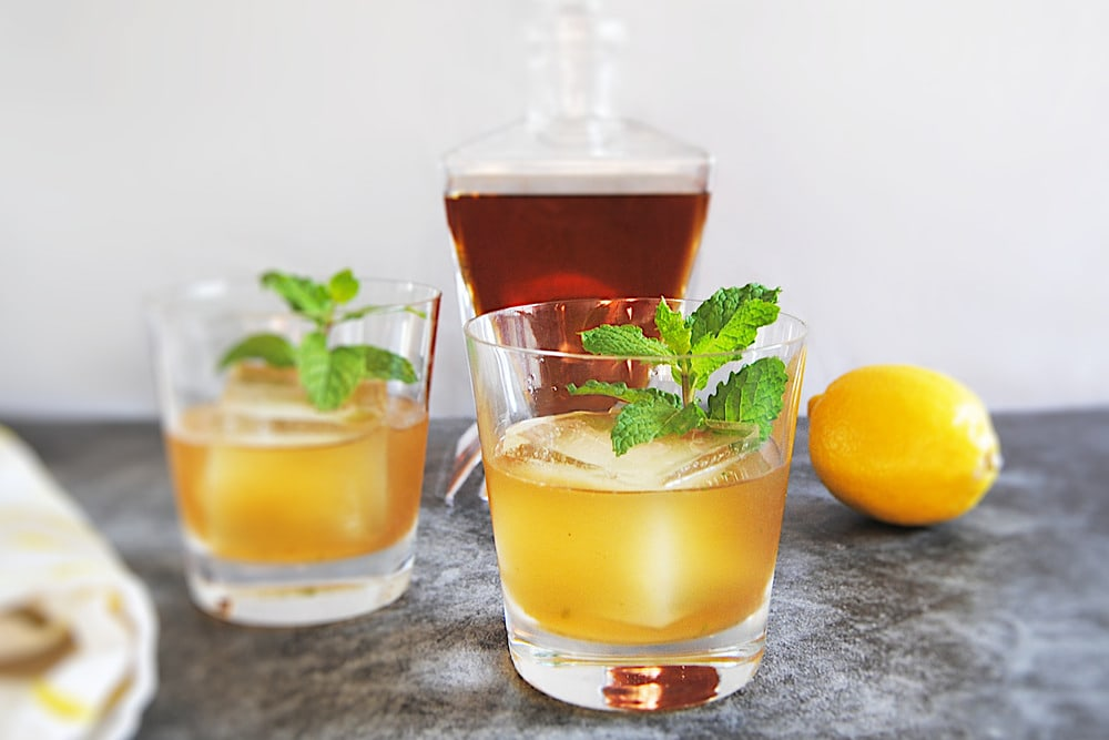 Two glasses filled with bourbon smash and mint garnish