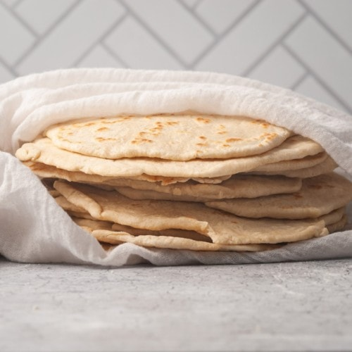 stack of homemade fluffy flour tortillas wrapped in a kitchen towel