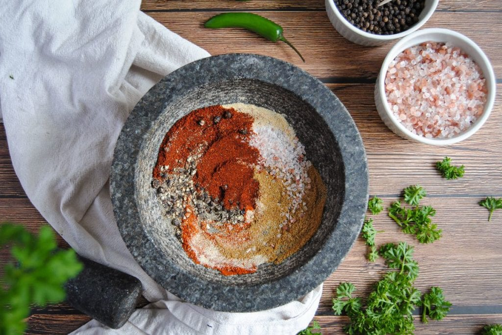 Overhead Image of chili and taco seasoning with parsley peaking through the side of the frame