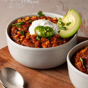 close up of a bowl of vegan chili with fresh toppings