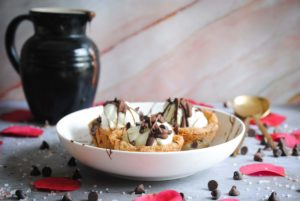 picture of three cookie dough cups for ice cream plated with pitcher behind it