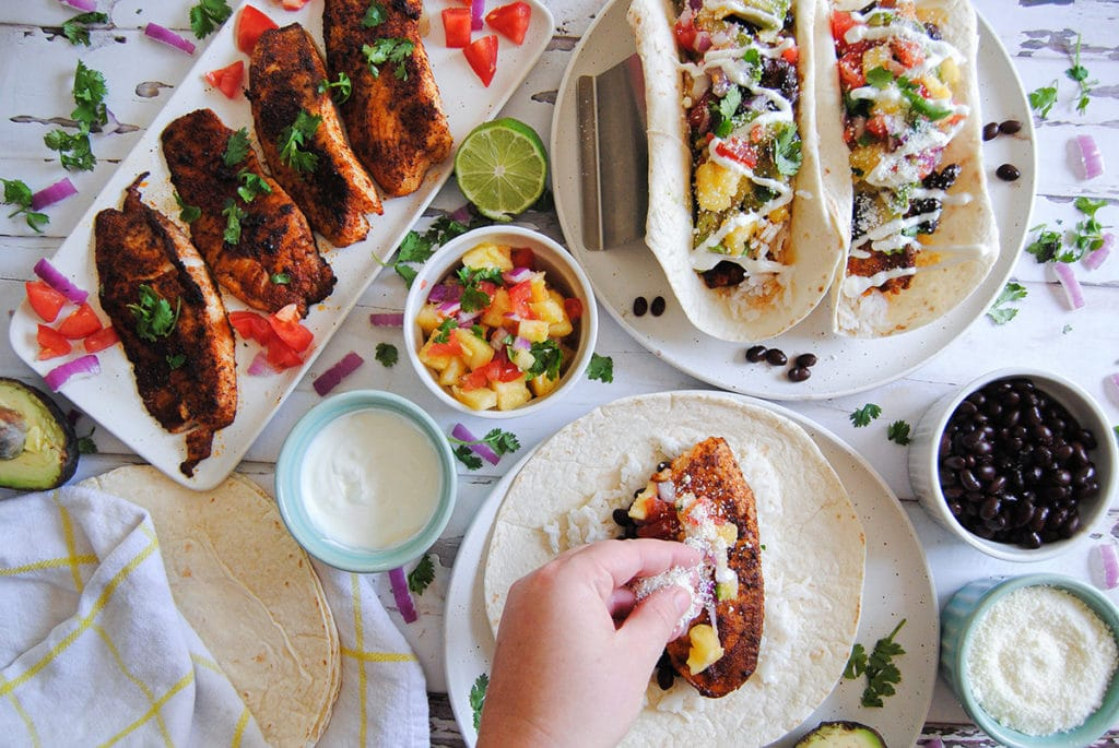 assembling a fresh fish taco with pineapple salsa