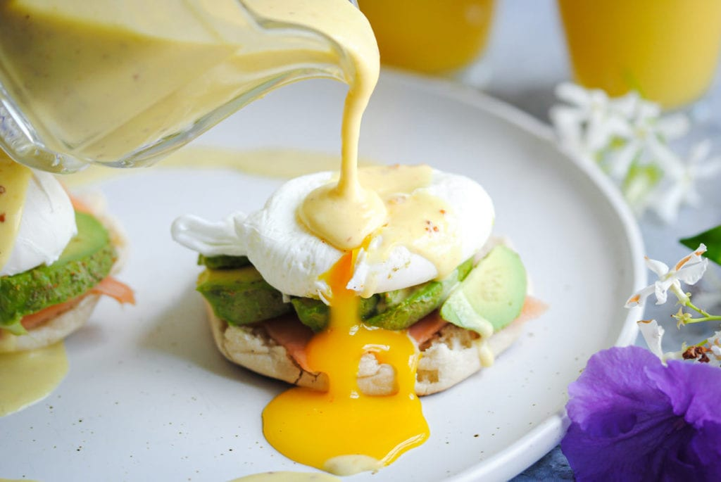 Pouring Hollandaise Sauce over poached egg with yolk dripping out