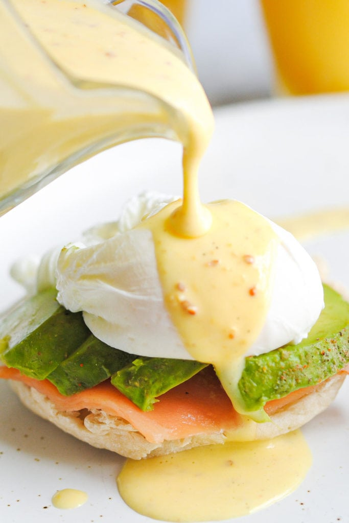 pouring hollandaise sauce over smoked salmon eggs benedict