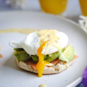 egg yolk dripping out of poached egg over avocado and english muffin