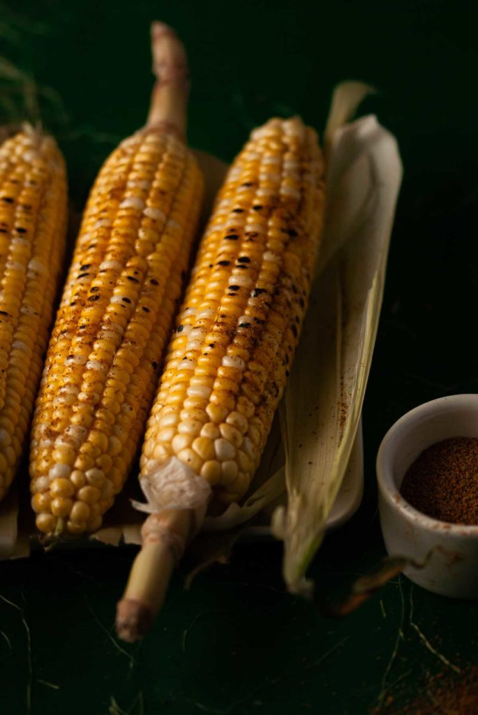 grilled corn on the cob laying on husks