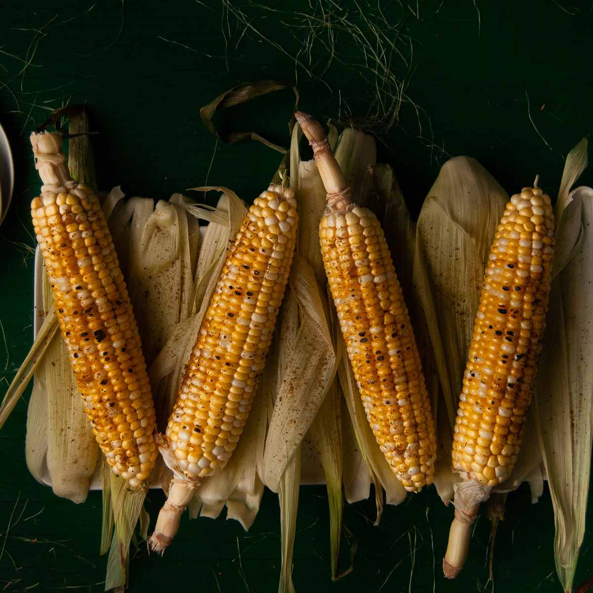 overhead shot of four ears of corn on the cob with old bay seasoning