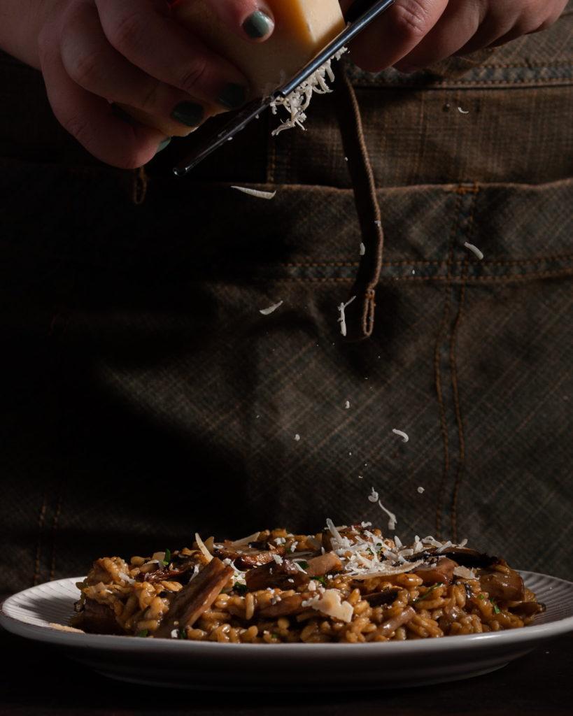 adding shaved parmesan to truffle mushroom risotto