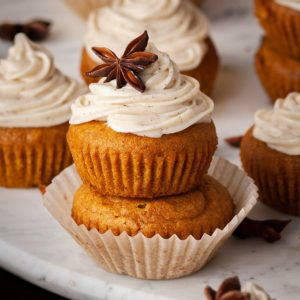 close up of two pumpkin muffins with cream cheese frosting stacked on top of each other