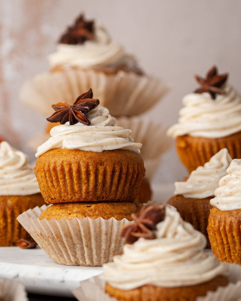 two pumpkin muffins stacked on top of eachother with the top oine having cream cheese frosting