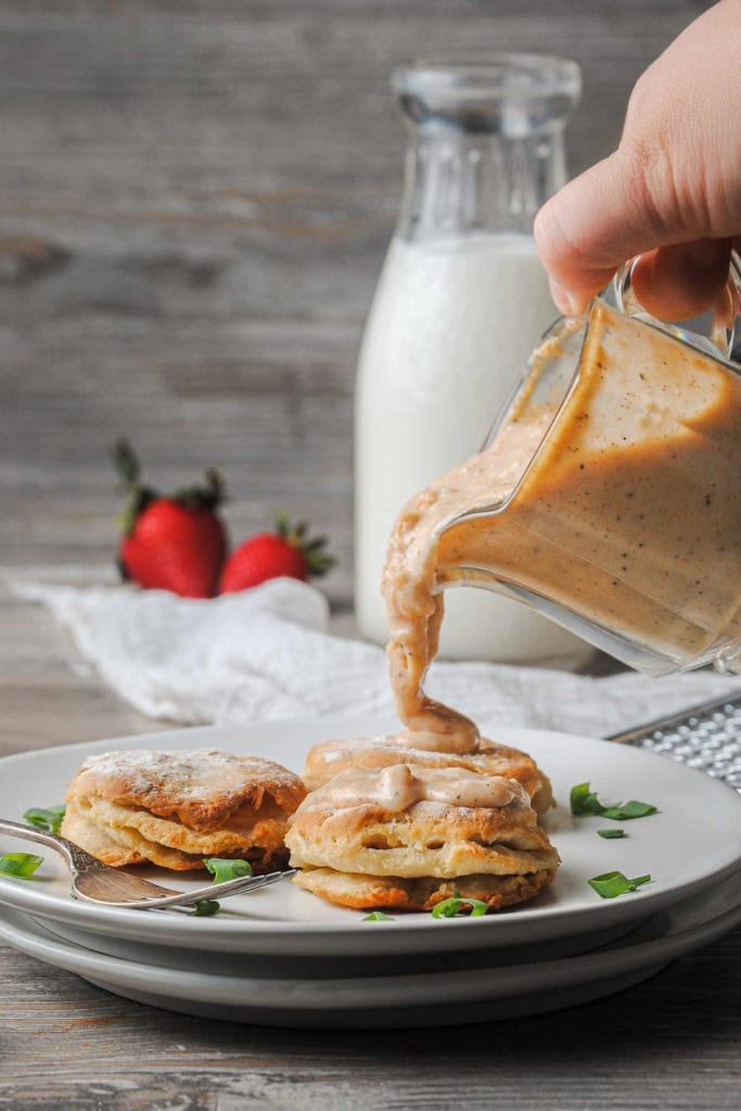 pouring vegetarian gravy over biscuits on a plate with scallions