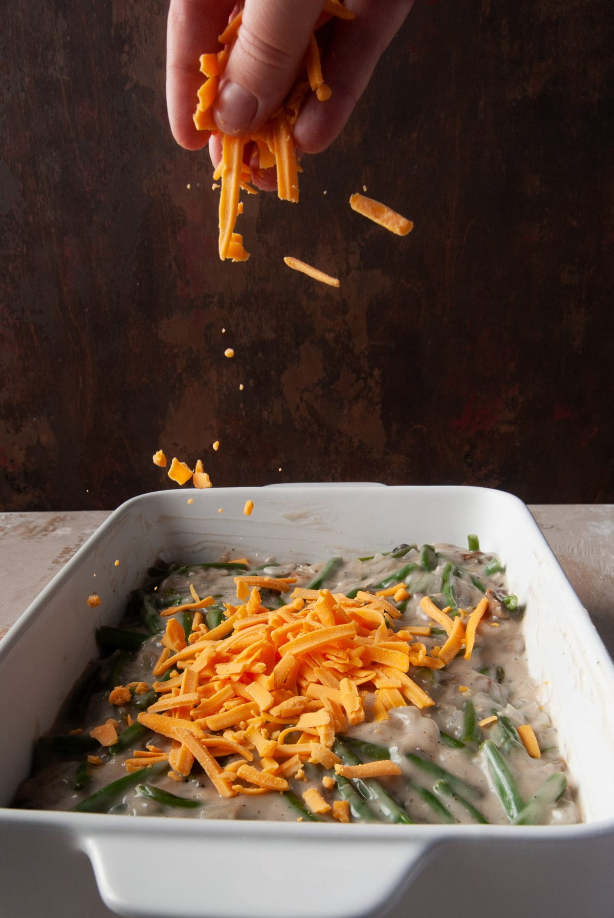 adding layer of cheddar cheese on top of green bean casserole