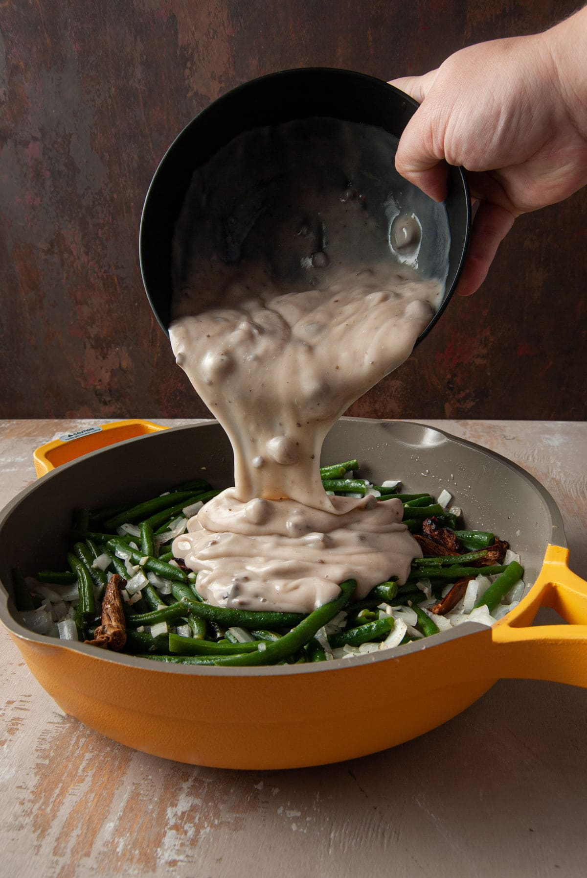 pouring cream of mushroom soup over vegetables cooking in pan
