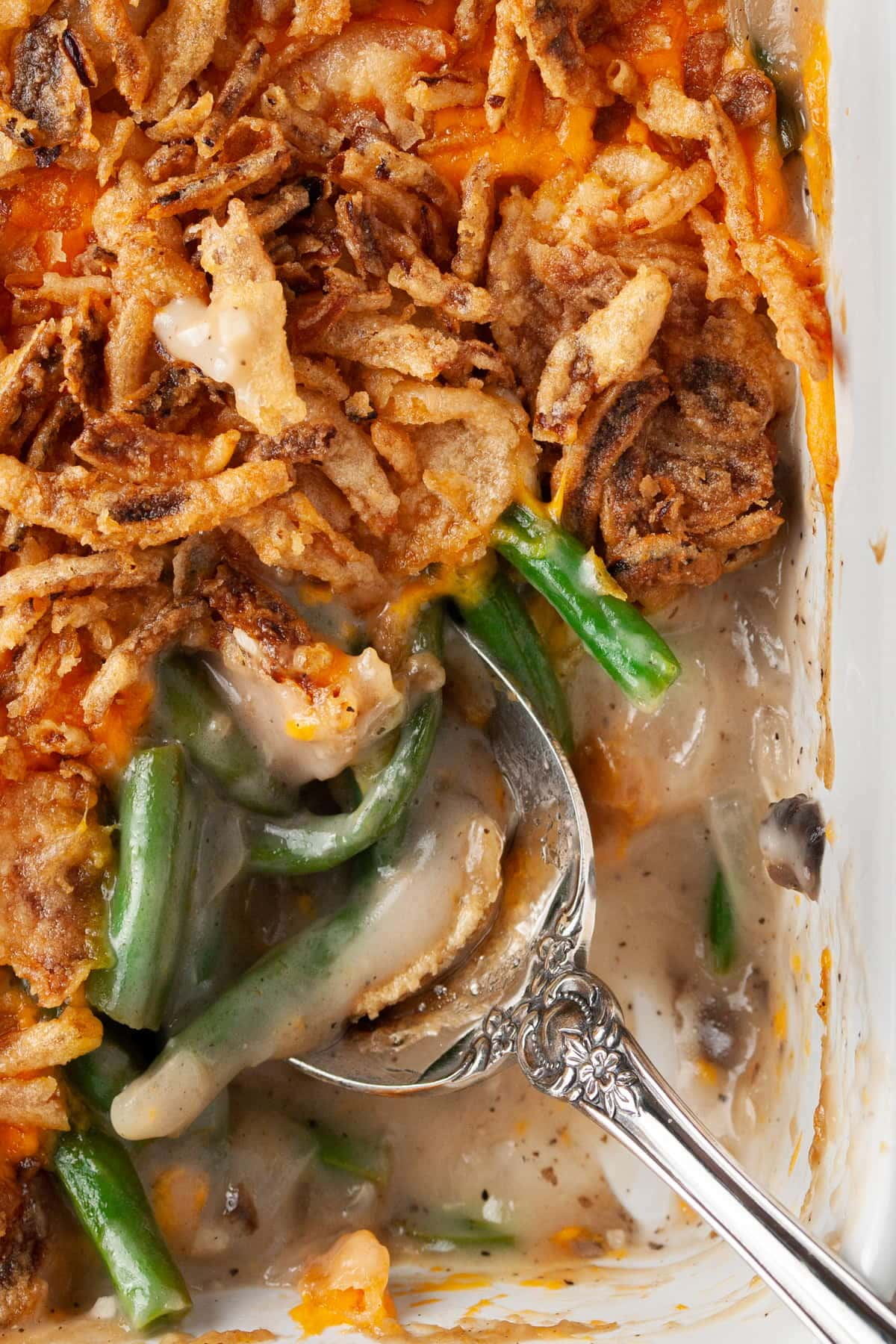 super close up of green bean casserole on a serving spoon
