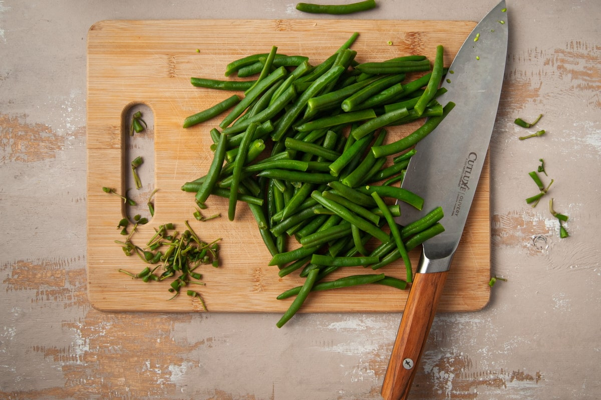 prepping greenbeans by chopping off ends and slicing in half