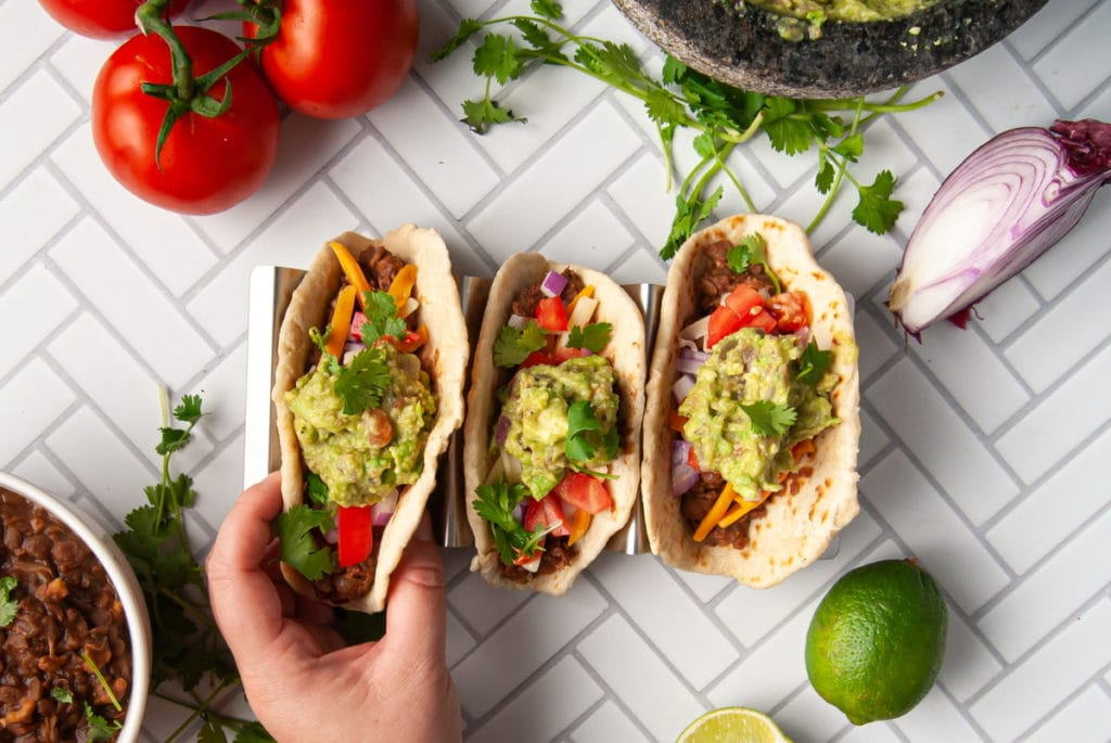 hand grabbing a meatless taco with toppings