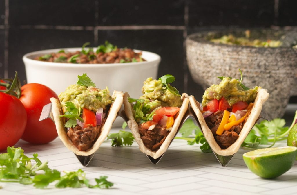 3 lentil walnut meat tacos in a taco holder with fresh toppings