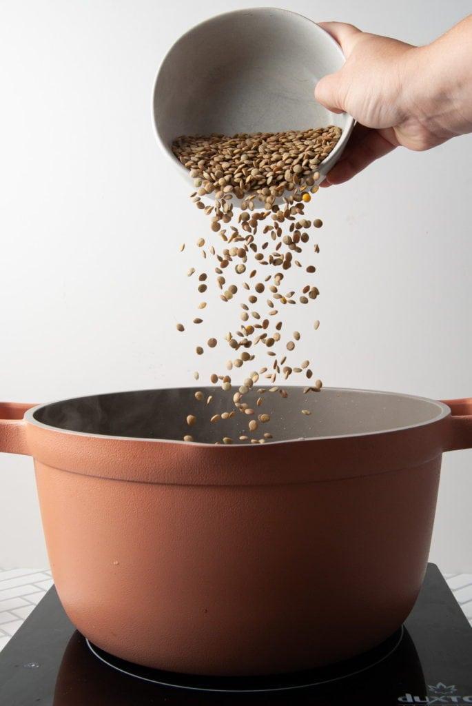 adding lentils to a pot