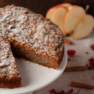 close up image of vegan apple cake with slice taken out to reveal moist inside of cake