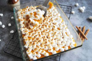Baking dish full of Maple Sweet Potato Casserole with a serving spoon scooping a spoonful out