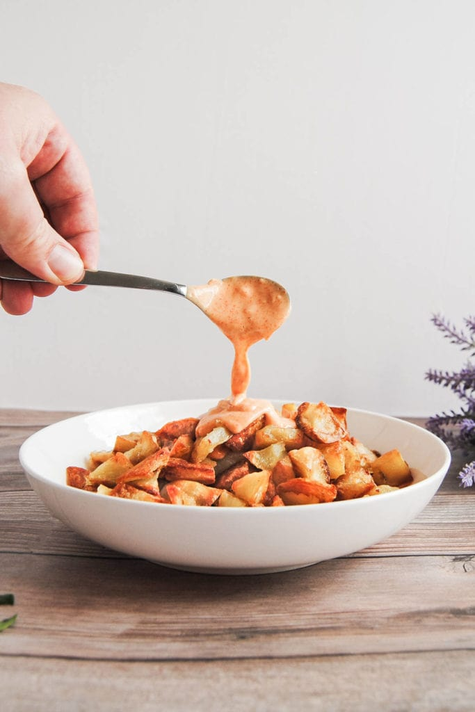 Crispy Potatoes with Spicy Sauce - Portrait With Spoon