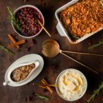 thanksgiving table full of exciting thanksgiving recipes - brandy cranberry sauce, green bean casserole with secret ingredient, mashed potatoes, mushroom gravy