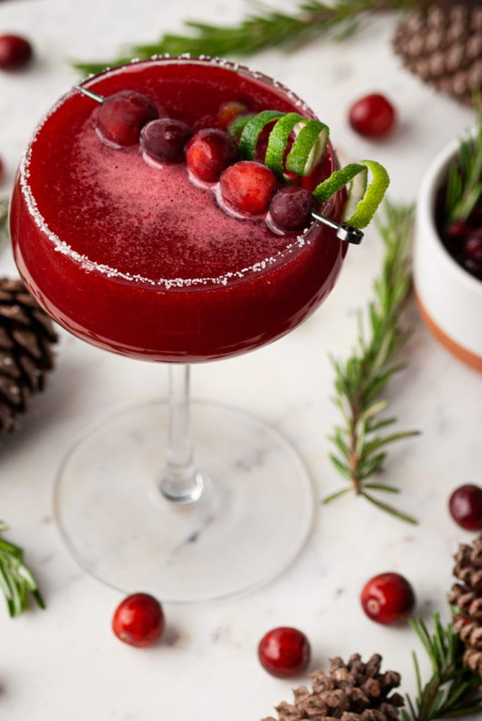 cranberry cosmo garnished with whole cranberries and twisted zested lime