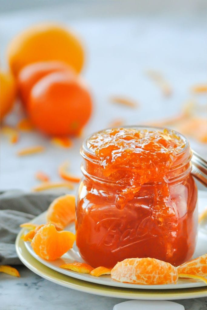 close up of jar with orange marmalade dripping out