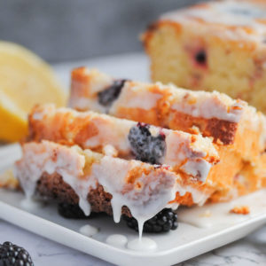close up of sliced lemon loaf with blackberries and glaze dripping off