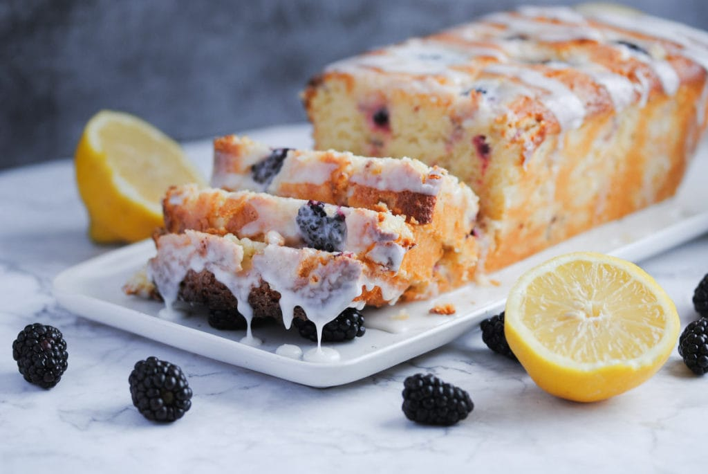 blackberry lemon loaf with 3 slices cut and lemon glaze dripping down