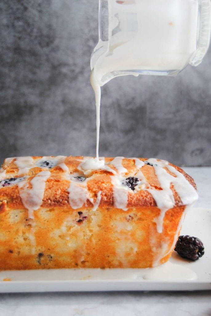 pouring lemon glaze over blackberry bread