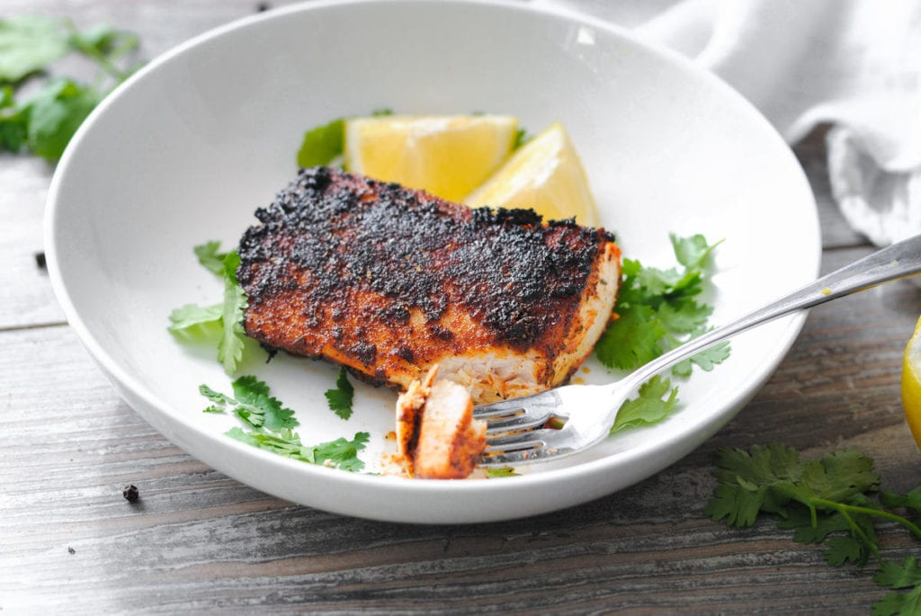 blackened fish with a bite cut off and on a fork