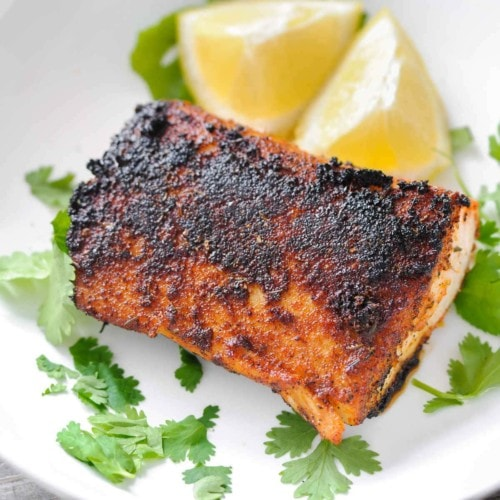 Plated Blackened Mahi-Mahi with lemon wedges and cilantro