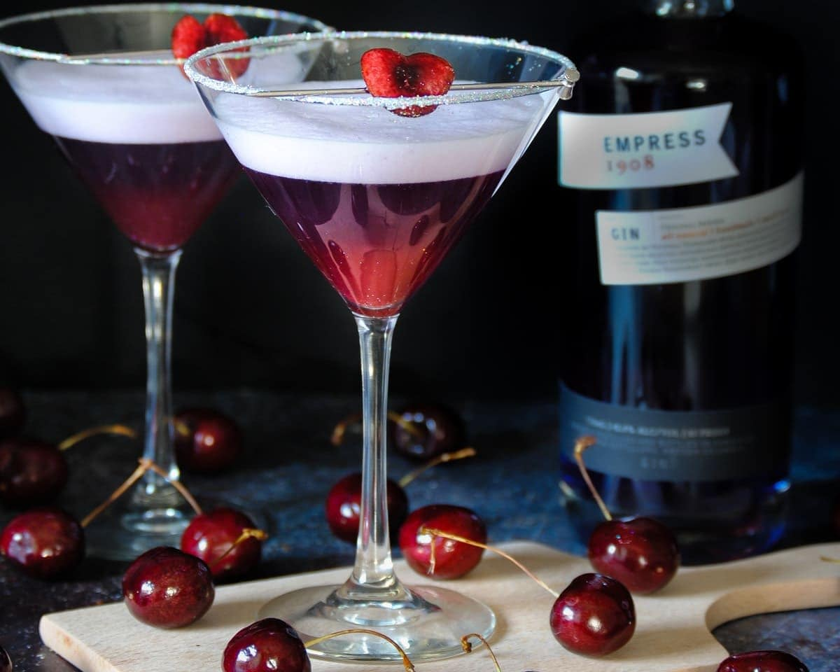 two cherry martinis with one on a wooden board