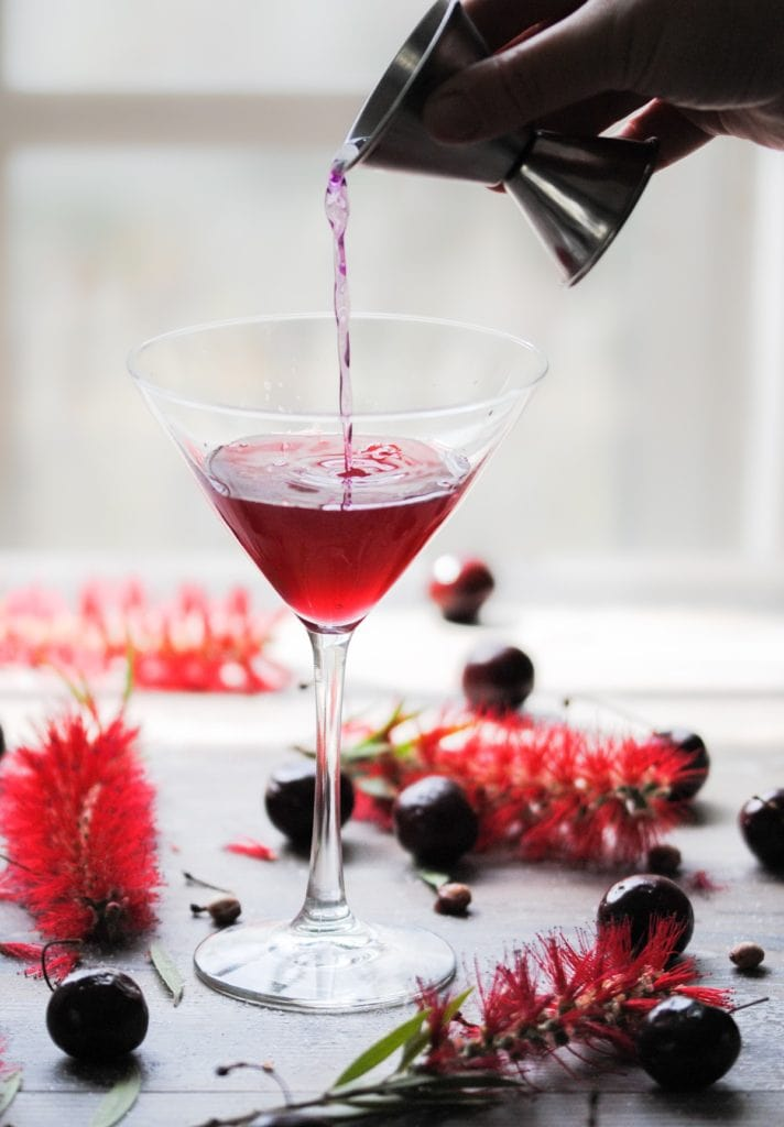 Pouring gin into cherry martini