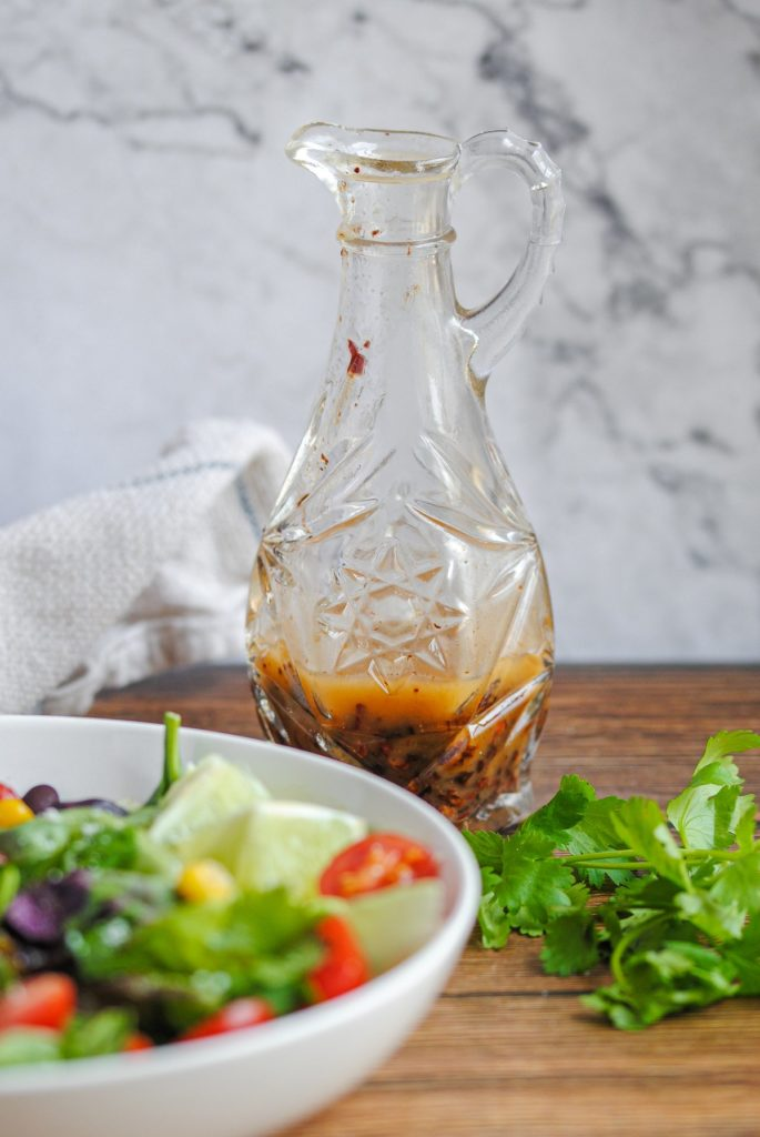chipotle vinaigrette in a crystal bottle sitting behind a colorful salad