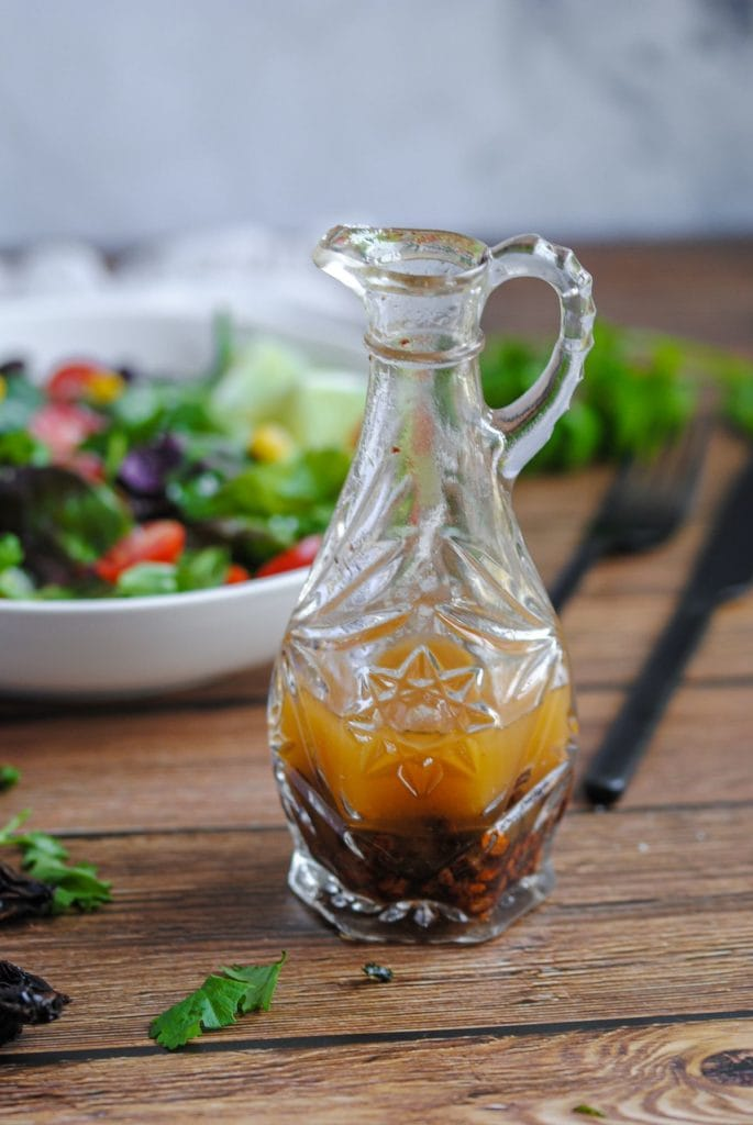 chipotle vinaigrette in a crystal bottle sitting in front of a fresh colorful salad