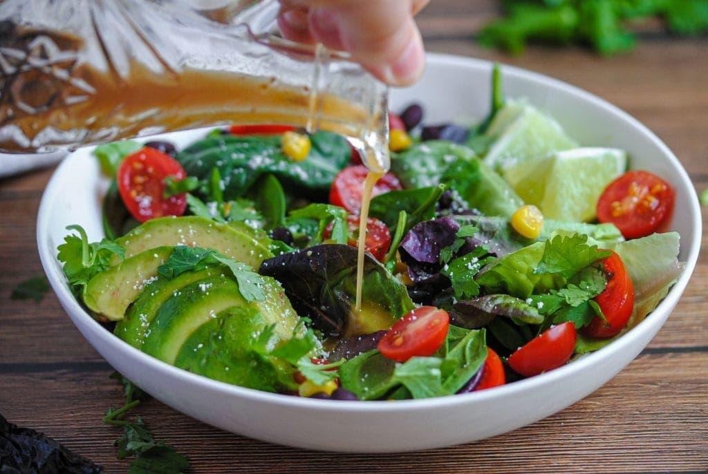 closeup of pouring vinaigrette on a salad