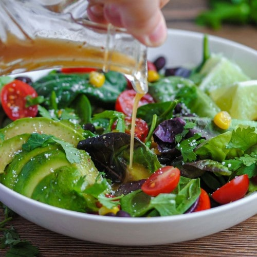 closeup of pouring vinaigrette on a salad