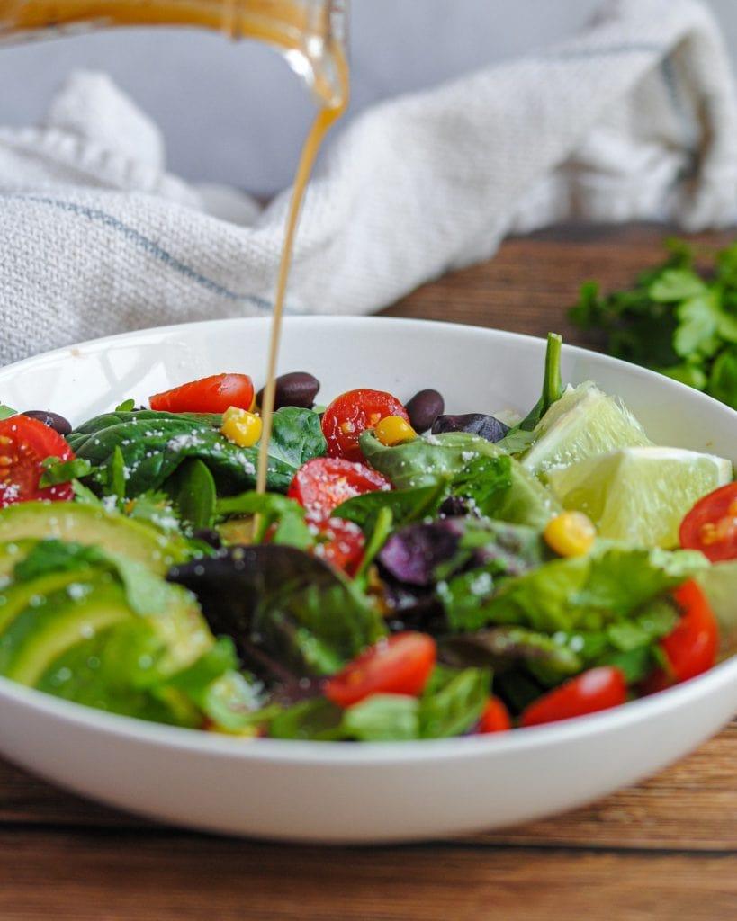 pouring vinaigrette onto a salad