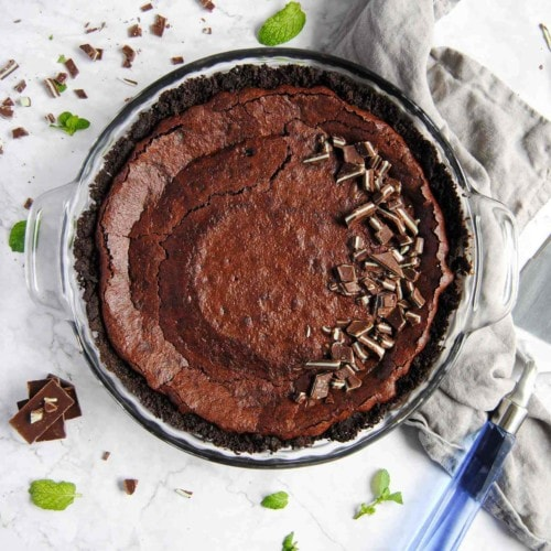 overhead shot of chocolate mint pie with oreo crust surrounded by fresh mint leaves and mint chocolates