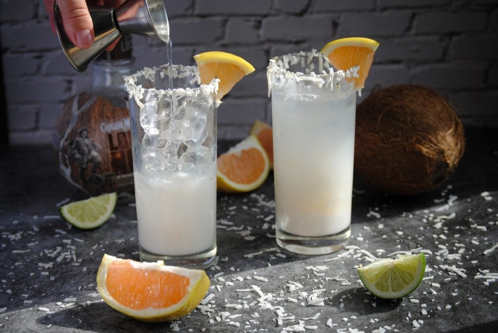 Pouring Coconut Water into glass of coconut rum