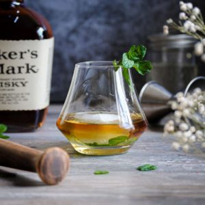 maker's mark mint julep cocktail surrounded by muddler and jigger