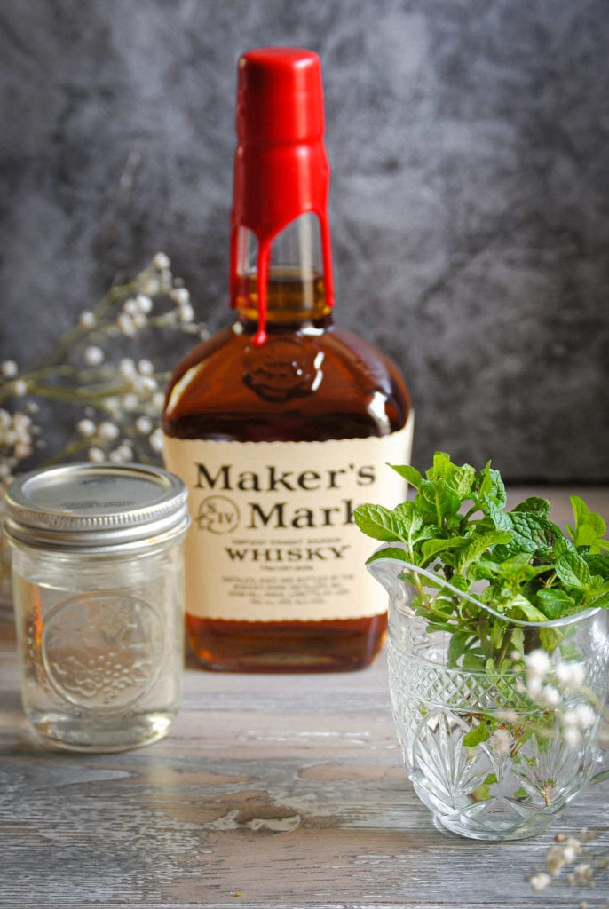 simple syrup in a jar and fresh mint in crystal with a maker's mark bottle in the background